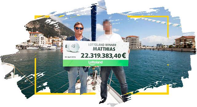 Ganador de Lotoland Matthias sostiene cheque con su premio