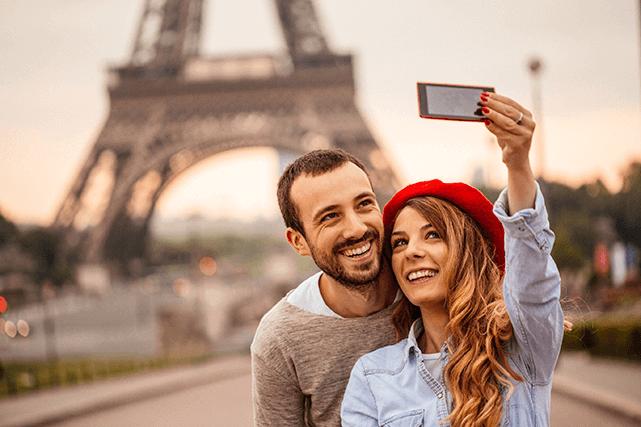 Una pareja feliz tomándose un selfie frente a la Torre Eiffel