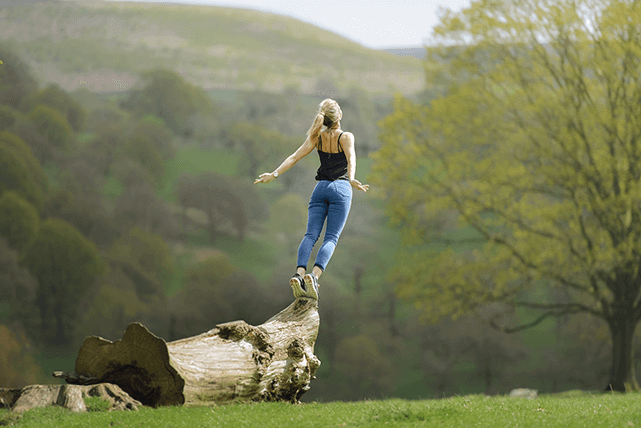 Mujer extiende sus manos y estira su cuerpo en la naturaleza