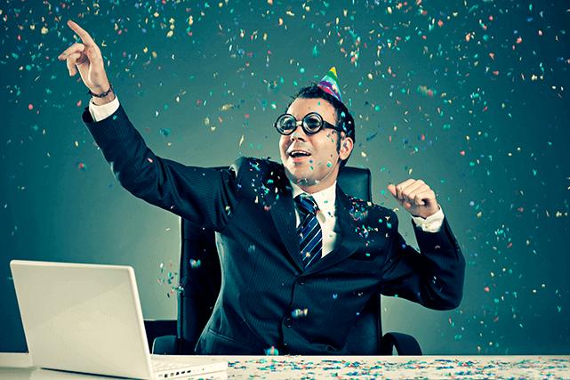 Hombre con corbata celebra en su escritorio feliz
