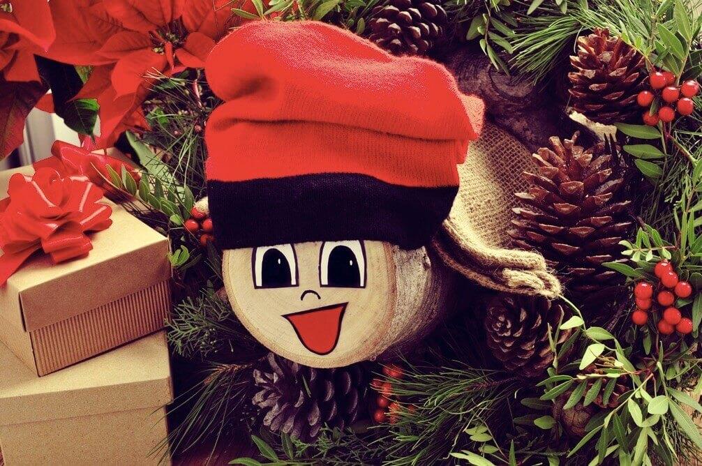Tronco de navidad sonriente, con un gorro rojo, rodeado de regalos.