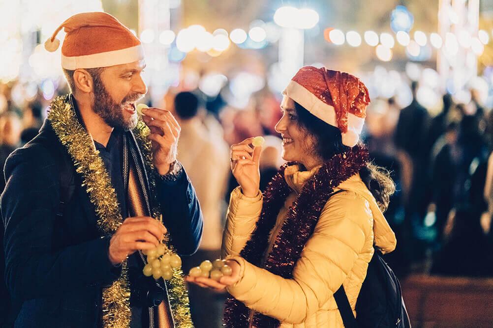 Dos personas comiendo uvas en Año Nuevo
